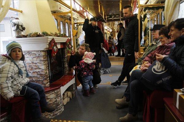 Utasok a kandallóval felszerelt, a Miskolc Városi Közlekedési Zrt. fényfüzérekkel feldíszített villamosán.