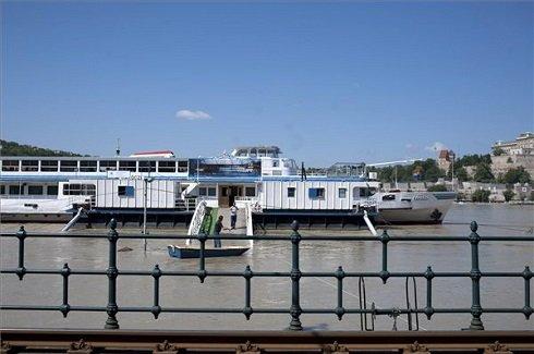 A Duna magas vízállása miatt csónakkal közelíti meg a Jane Haining rakpartnál kikötött Rákóczi hajót egy férfi 2013. június 8-án. MTI Fotó: Kallos Bea