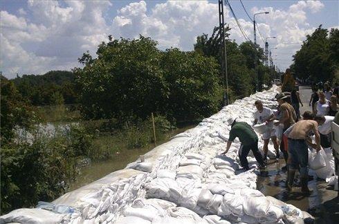 A 11-es főútat homokzsákokkal védik Leányfalu határában 2013. június 8-án. Az árvízvédelmi munkálatok, valamint a vízátfolyások miatt a 11-es főút több szakaszán is teljes, vagy félpályás zárás van érvényben, így például Szentendrén, Leányfalun, Dunabogdánynál, Visegrádnál, Dömösnél és Pilismarótnál. MTI Fotó: Éder Vera