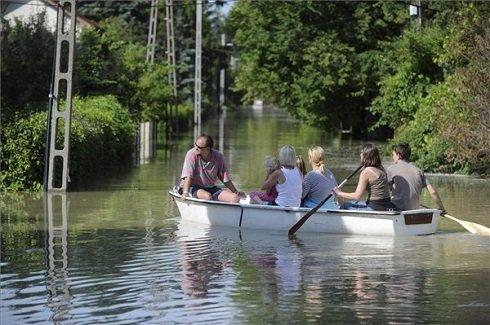Csónakkal közlekedő család a Duna áradása miatt vízben álló utcában Szentendre és Leányfalu között 2013. június 9-én. MTI Fotó: Mihádák Zoltán