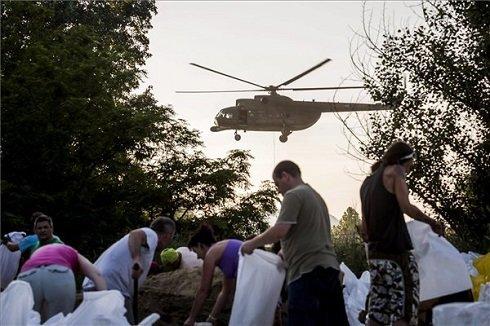 Önkéntesek homokzsákokat töltenek Szigetmonostoron, melyeket helikopterrel szállítanak Horányba 2013. június 9-én. A település külterületén átbukott a víz, és az erdei mélyvonulaton keresztül áramlik a szigetmonostori üdülőterület felé, ahonnan 162 embernek kellett elhagynia az otthonát. MTI Fotó: Mohai Balázs