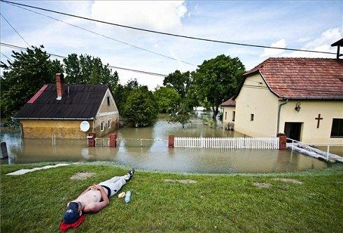 Önkéntes pihen Szőgye határában, a vízben álló házak mellett 2013. június 9-én. Győr-Moson-Sopron Megyében már elkezdett a Duna szinje apadni. MTI Fotó: Krizsán Csaba
