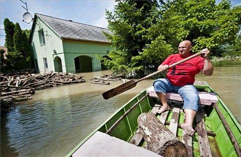 Kecskeméthy Gábor víz alatt álló házát nézi csónakból Szőgye határában 2013. június 9-én. Győr-Moson-Sopron Megyében már elkezdett a Duna szinje apadni. MTI Fotó: Krizsán Csaba