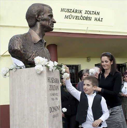 Huszárik Kata színésznő, Huszárik Zoltán lánya és unokája, Gergő virágot helyez el Monostori Sebestyén Huszárik Zoltán rendezőről készült mellszobrán a Pest megyei Domonyban 2013. október 13-án. A Huszárik Zoltán halálának 32. évfordulójára készült szobor felavatása mellett a posztumusz Kossuth-díjas filmrendező, grafikus nevét viseli ezentúl szülőfalujának művelődési háza is. MTI Fotó: Kallos Bea