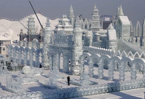 Egy látogató fényképezi a jégből készült épületeket - Fotó: Reuters