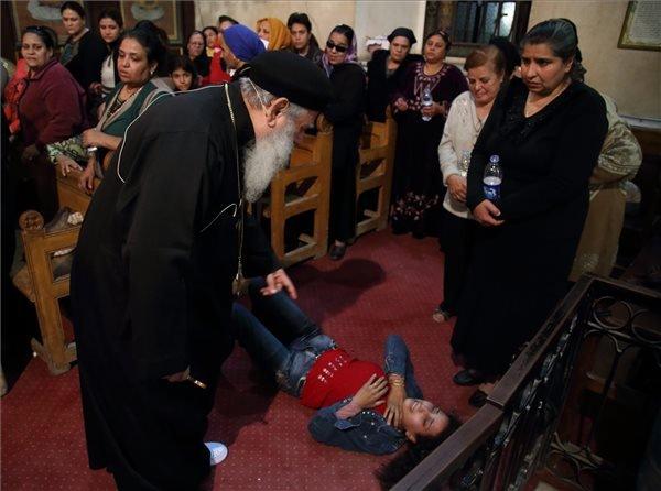"""Makári atya ördögöt űz egy keresztény hívőből a kairói főpályaudvar közelében található nagytemplomban 2014. október 9-én. Egyiptomban nagyon sok muzulmán és keresztény számára természetes, hogy pszichés panaszaikkal ördögűzőhöz fordul, s a megfelelő """"szakember"""" kiválasztásakor a vallások közti rideg határok meglepően rugalmassá válnak. MTI Fotó: Máté Bence"""