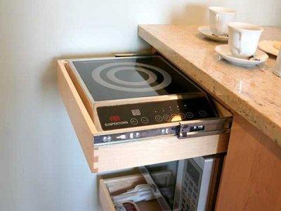 Parányi konyhák rejtett tűzhelye étkezőasztalba építve.