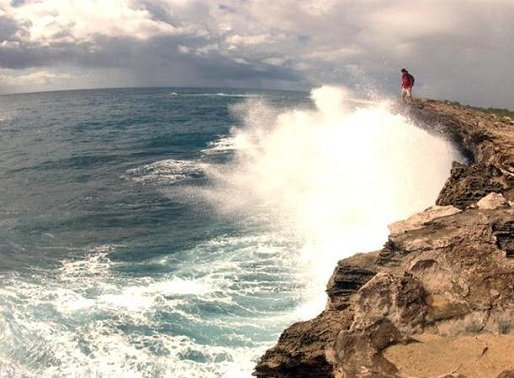 Man standing on cliff edge watching ocean waves splashing, Hawaii