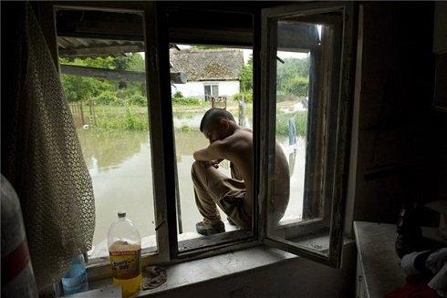 Egy fiú ül lakóházának ablakában a Tolna megyei Bátán 2013. június 11-én. A településnél reggel 761 centiméteres vízállást mértek a Dunán. A tetőzés június 12-én délután 775 centiméteren várható, az előre jelzett szint 34 centiméterrel haladhatja meg a 2002-es árvíz idején mért, eddigi legmagasabb, 741 centiméteres vízállást. MTI Fotó: Koszticsák Szilárd