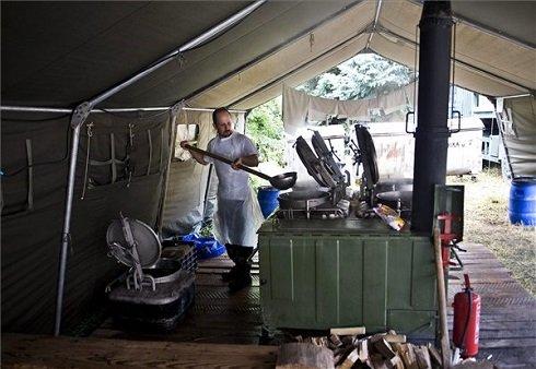 Vizet melegít egy katona a tábori konyhán, ahol  készül az ebéd az árvízi védekezésben részt vevő katonáknak Kalocsán 2013. június 11-én. A Tábori Ellátó Csoport 1500 fő elhelyezését, élelmezését és kiszolgálását tudja biztosítani. MTI Fotó: Ujvári Sándor