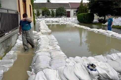 Homokzsák medencével lokalizálják a feltörő vizet Nagymaroson 2013. június 9-én. A Duna ismét betört a nagymarosi Váci utcába, ahol a víz három-négy házat kerített körbe, a lakókat kimenekítették. MTI Fotó: Beliczay László
