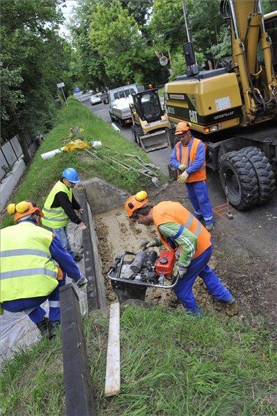 A Fővárosi Csatornázási Művek Mélyépítő Kft. szakemberei az úgynevezett védvonali áttörések, azaz az árvízi kapukat zárják le az óbudai Királyok útján 2013. június 4-én. Budapesten másodfokú árvízvédelmi készültséget rendeltek el, az eddigi legmagasabb vízszint, 860 centiméter körül tetőzhet a Duna. MTI Fotó: Kovács Attila