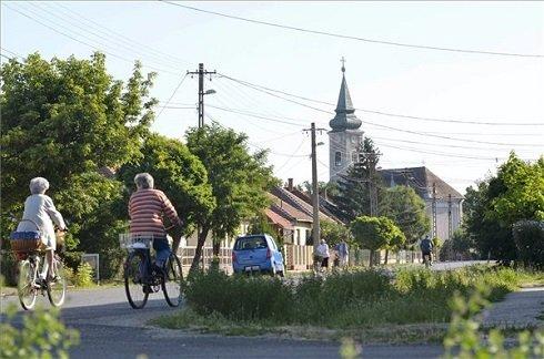 Kerékpárosok a Jász-Nagykun-Szolnok megyei Besenyszögön 2013. július 12-én. Besenyszög azon tizennyolc település egyike, amelynek városi címet adományozott a köztársasági elnök 2013. július 15-ei hatállyal. MTI Fotó: Mészáros János