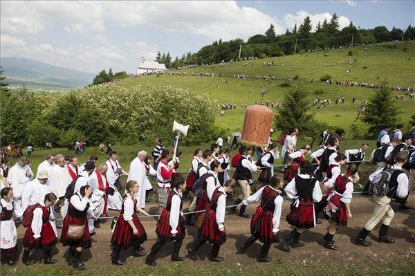 A Kis- és Nagysomlyó-hegy közötti nyeregben felállított oltárhoz érkező zarándokok Csíksomlyón 2014. június 7-én. Középen a labarum, a csíksomlyói búcsú legfőbb jelvénye. MTI Fotó: Koszticsák Szilárd
