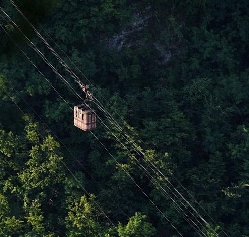 Az ütött-kopott kabin a fák felett szállítja utasait.
