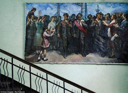 Még ma is a kommunista időket idézi az állomás épületének falán a festmény.