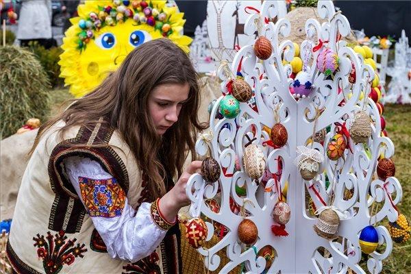 Hucul népviseletbe öltözött leány tojáskompozíciót készít a kárpátaljai Ungváron rendezett szabadtéri húsvéti kiállításon.