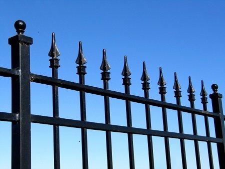 A fém kerítés a legelterjedtebb, amelynek rúdjai hegyes lándzsa végűek. A betolakodók talán meggondolják, hogy behatoljanak-e a portára.