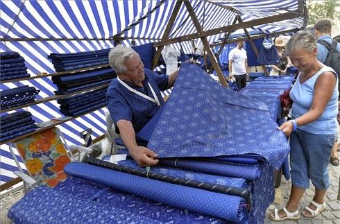 Kovács Miklós tiszakécskei kékfestő kelméit mutatja egy érdeklődőnek a Mesterségek ünnepén, a budai Várban 2013. augusztus 17-én. MTI Fotó: Máthé Zoltán
