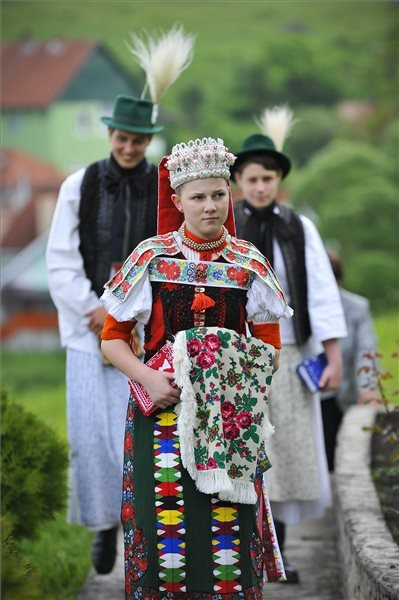Kalotaszegi népviseletbe öltözött fiatalok érkeznek a pünkösdvasárnapi istentiszteletre az erdélyi Körösfő református templomába 2015. május 24-én. MTI Fotó: Czeglédi Zsolt