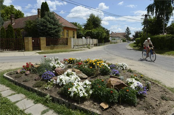 Virágok és egy biciklista a Dózsa György úton, a Pest megyei Sülysápon 2013. július 12-én. Sülysáp azon tizennyolc település egyike, amelynek városi címet adományozott a köztársasági elnök 2013. július 15-ei hatállyal. MTI Fotó: Kovács Tamás